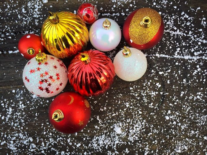 Red and white glittering Christmas globes on rustic wooden table powdered with snow High Angle View No People Multi Colored Celebration Freshness Day Close-up Winter Snow Season  Holiday Festive Celebrate Decorations Glitter Christmas Globes Round Hang Rustic Wooden Table Christmas Globes