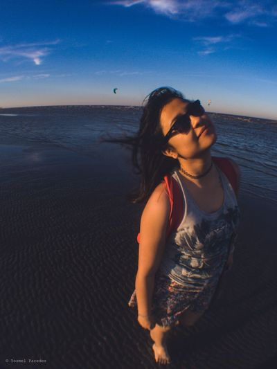 Beautiful woman on beach against sky
