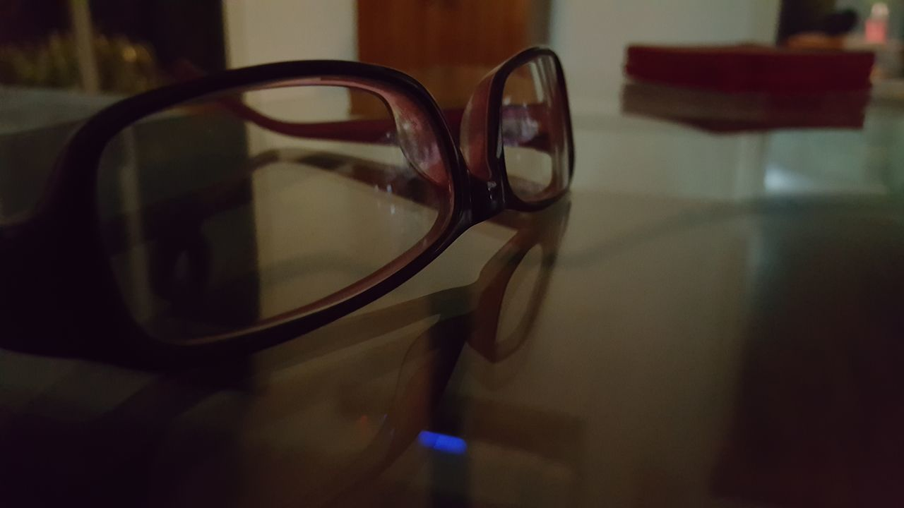 glasses, eyeglasses, table, close-up, focus on foreground, still life, eyesight, indoors, reflection, transparent, no people, personal accessory, glass - material, sunglasses, absence, fashion, seat, chair, single object, day, eyewear