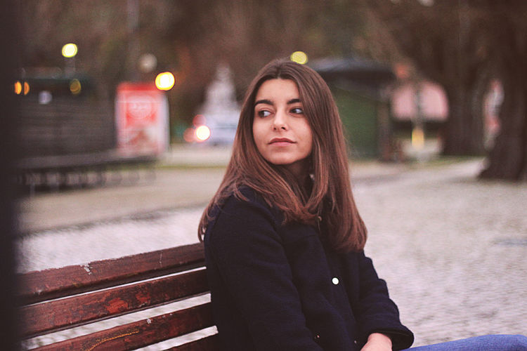 Young woman looking away while sitting on bench at park during winter