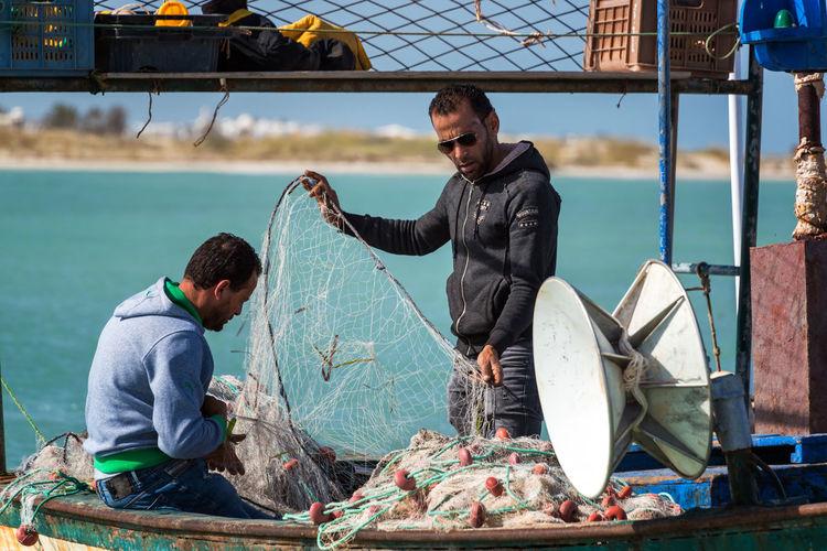 Man fishing in boat at sea shore