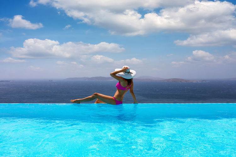 Woman sitting at infinity pool against sea