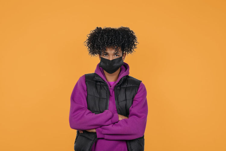 Portrait of young man wearing mask standing against orange background