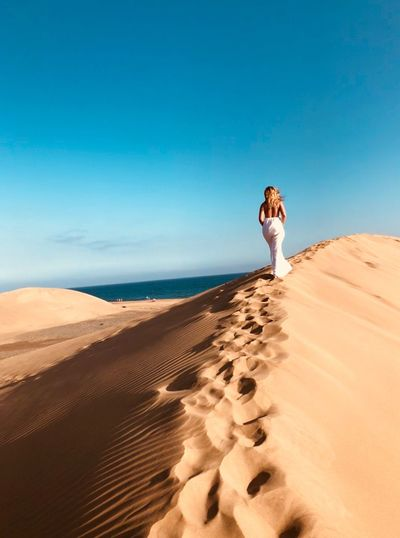 Rear view of woman walking on sand dune in desert against blue sky