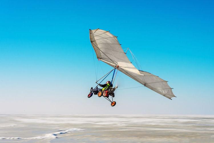Man paragliding over sea against blue sky