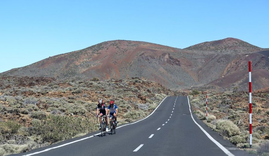 Men Riding Bicycle On Road Against Clear Sky