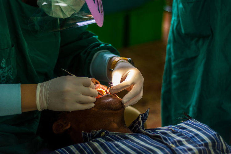Midsection Of Male Dentist Operating Patient In Hospital