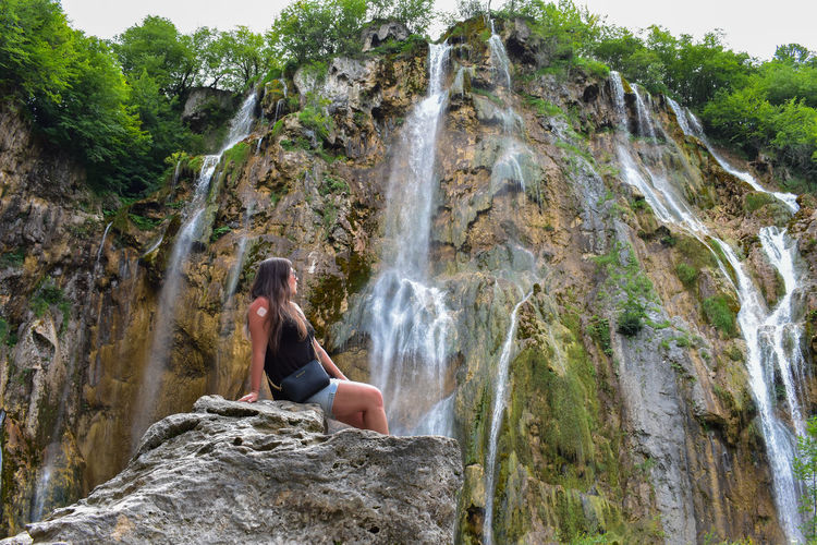 Low angle view of mid adult woman wearing sunglasses sitting on rock against waterfall