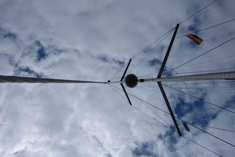 Low angle view of bird on cable against cloudy sky