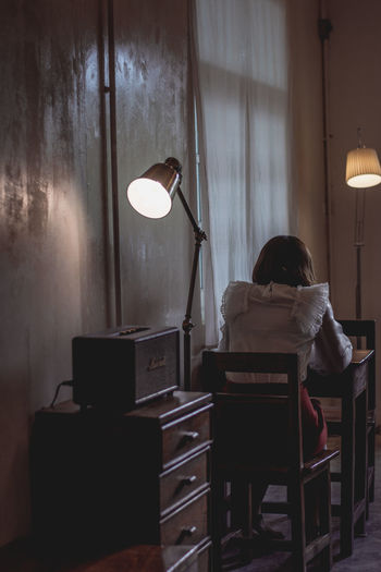 Rear view of woman sitting on table in illuminated room