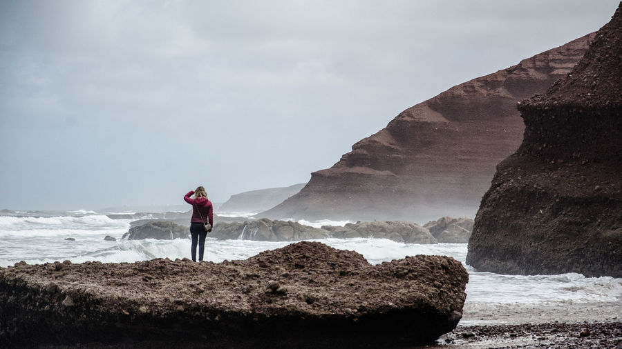 Rear View Of Woman Standing On Rock Formation By Sea Against Sky