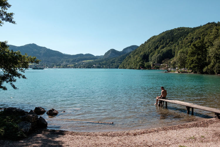 Austria Holiday Man Salzkammergut Summertime Swimming Beachday Beauty In Nature Crisp Day Jetty Lake Landscape Lush Mountain Nature One Person Outdoors Real People Scenics Sky Summer Water Wolfgangsee Young Adult