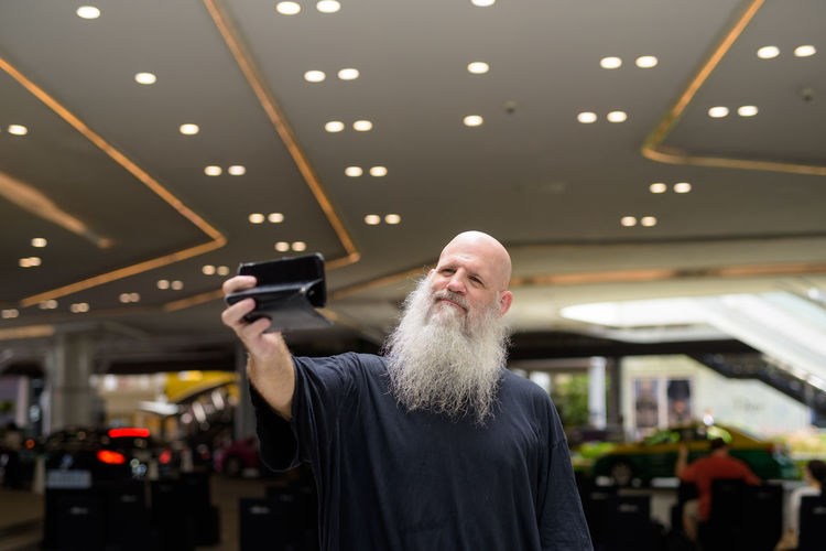 Man holding camera while standing on illuminated ceiling