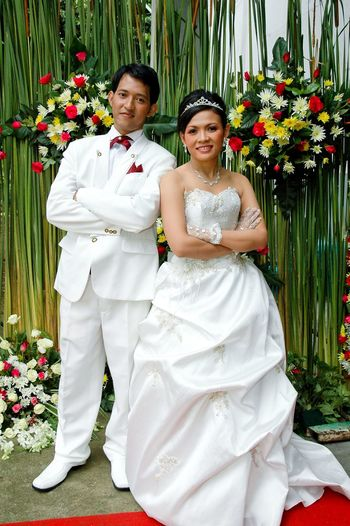 Portrait of bride and bridegroom with arms crossed standing