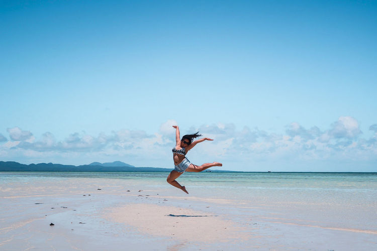 Young woman jumping at beach against blue sky