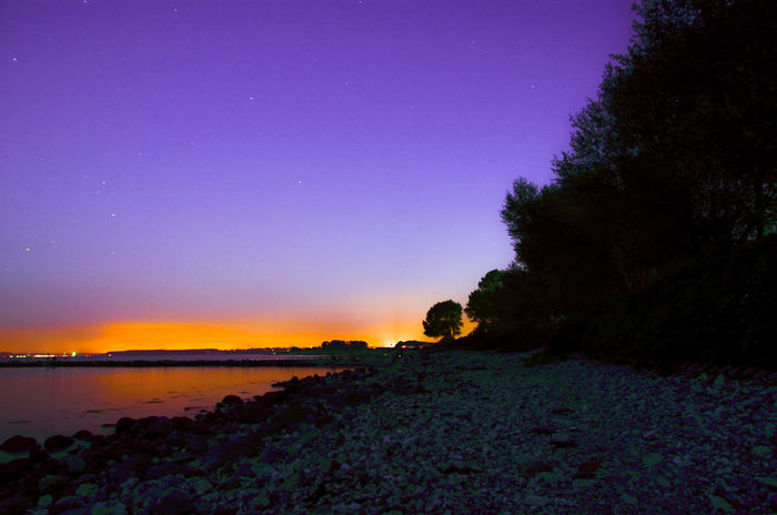Beach At Night Beach Scenics Night Nature Beauty In Nature Sky Purple Tranquility Tranquil Scene Landscape No People Sea Water Outdoors Horizon Over Water Orange Lila Lilac Blue Colorful Sky Trees On The Beach Tree Trees Trees And Sky