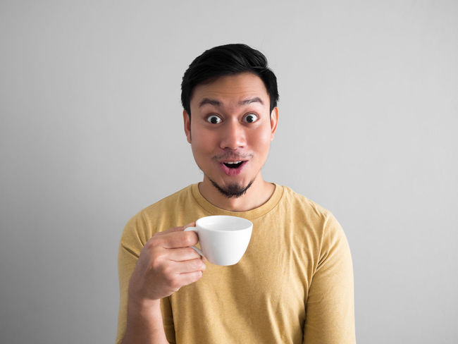 Asian man drinks coffee with funny expression face. Asian  Cup Drink Fun Funny Happy Holding Man People Portrait Shock Smile Studio Shot Thai