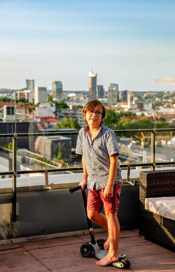 Full length of man standing against railing in city