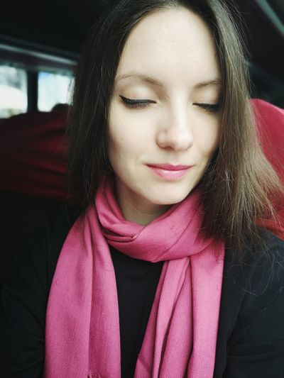 Close-up of smiling woman with eyes closed sitting in bus