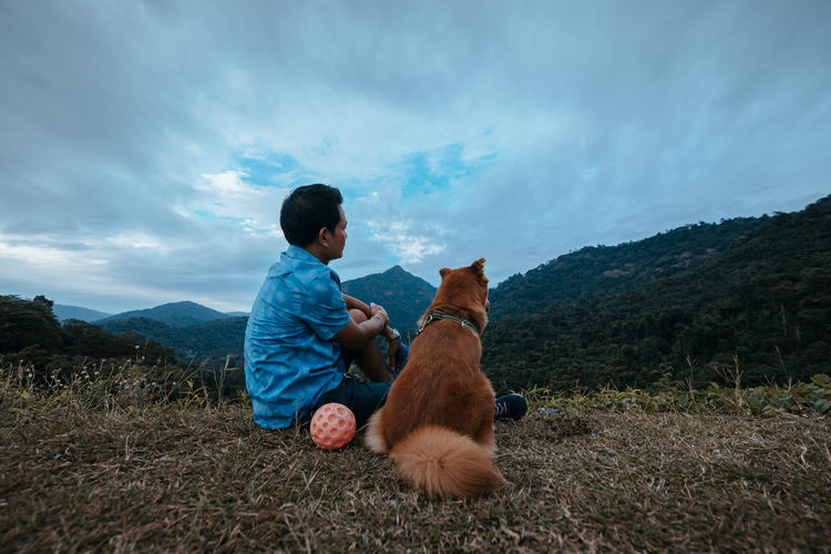 Rear view of man with dog sitting on land