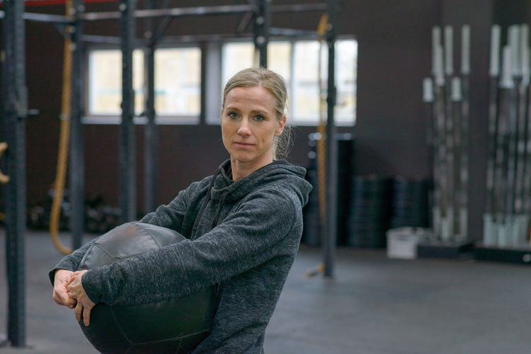 Portrait Of Mature Woman Holding Fitness Ball At Gym