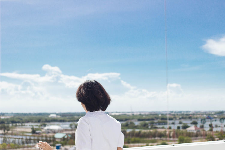 young woman wearing student uniform standing and waving hand at the rooftop under blue cloudy sky with copy space Adult Building Exterior Childhood Cityscape Cloud - Sky Day Leisure Activity Nature One Person Outdoors People Real People Rear View Sky Women