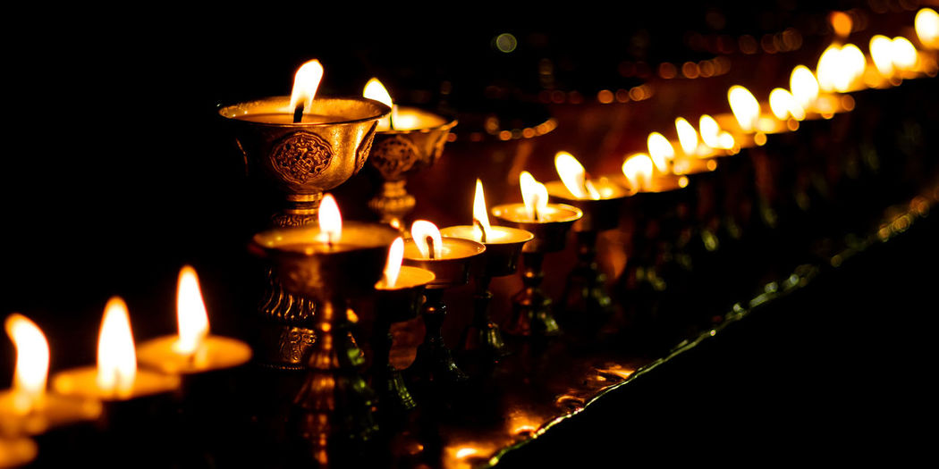 Tibet butter lamp Flame Illuminated Lighting Equipment Burning Glowing Reflection Oil Lamp Igniting Candle Heat - Temperature Close-up Spirituality No People Tradition Religion Place Of Worship Cultures Indoors  Paper Lantern Black Background