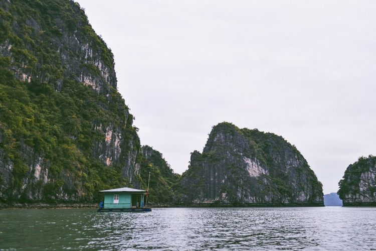 Houseboat By Mountain In Halong Bay Against Clear Sky