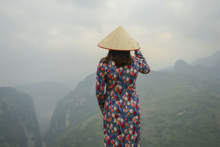 Rear view of woman wearing conical hat while looking at mountain range