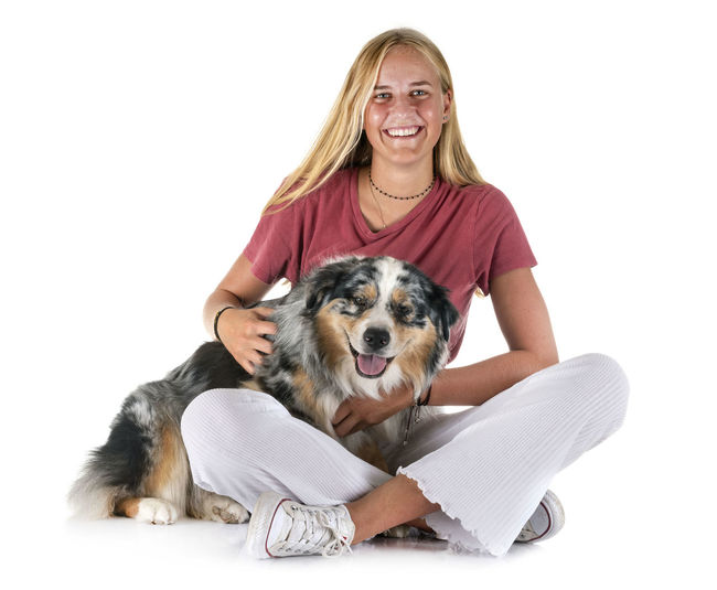 Portrait of smiling young woman with dog against white background