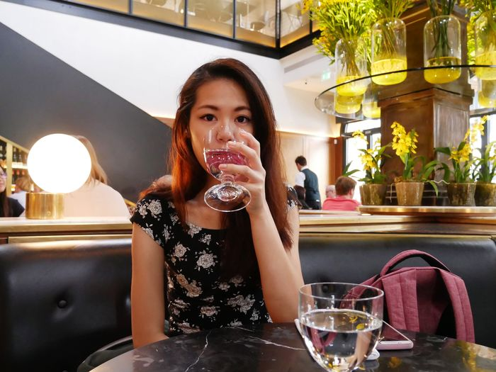 Portrait of a woman drinking glass in restaurant