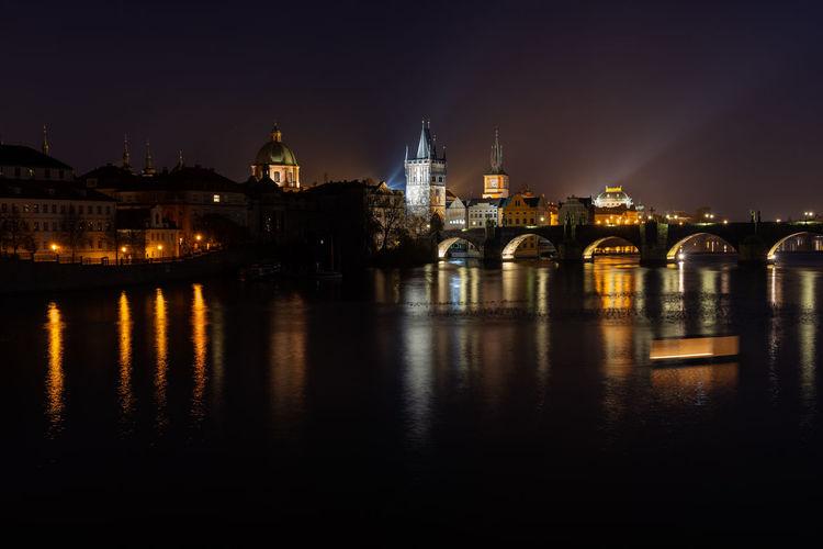 Scenic view of illuminated prague skyline at night. charles bridge across vltava river