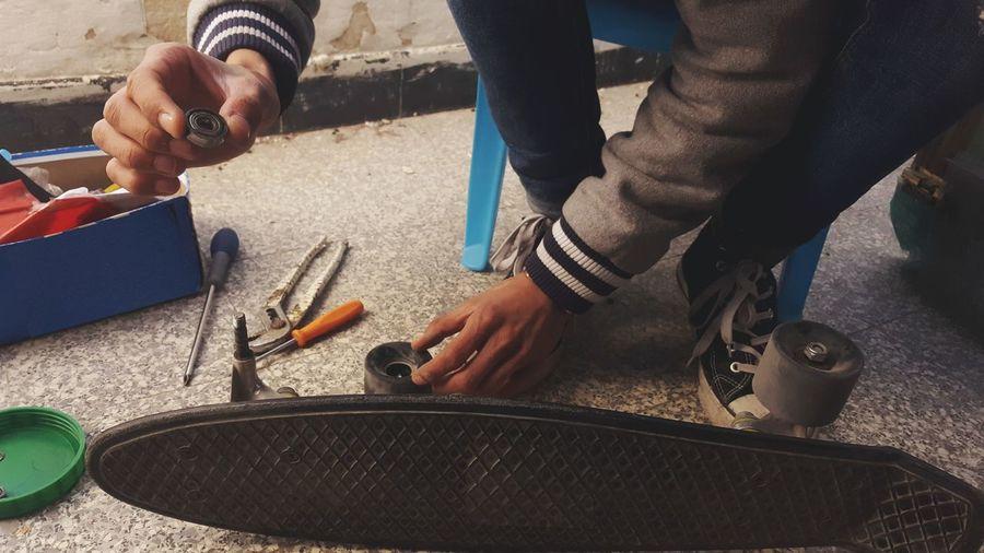 Low section of man repairing skateboard