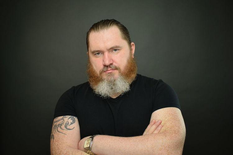 Portrait of mid adult man against black background