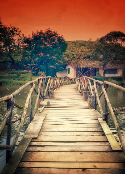 Empty wooden footbridge against sky