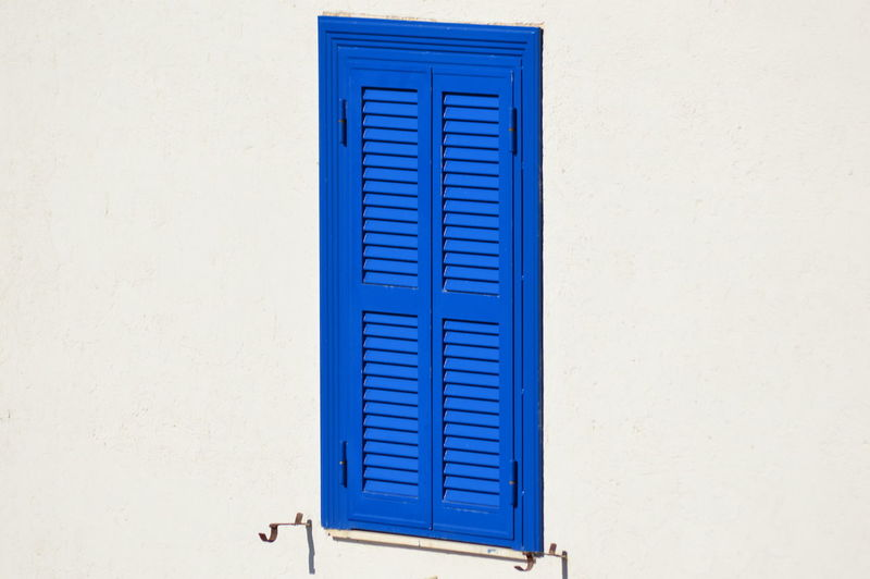 A blue shutter on a white wall Architecture City Wall Beauty In Nature Blue Shutter Citycape Daylight House Italy Shutter White White Wall Window Zoom