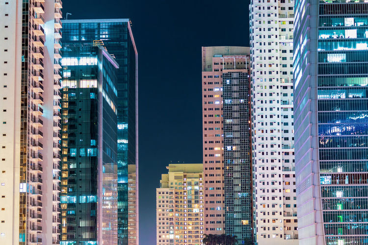 Low angle view of illuminated buildings in city at night