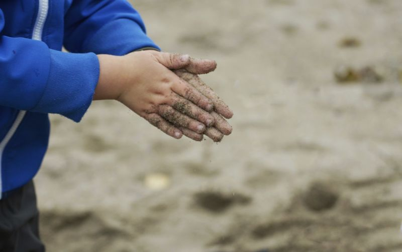 Midsection of child spilling sand