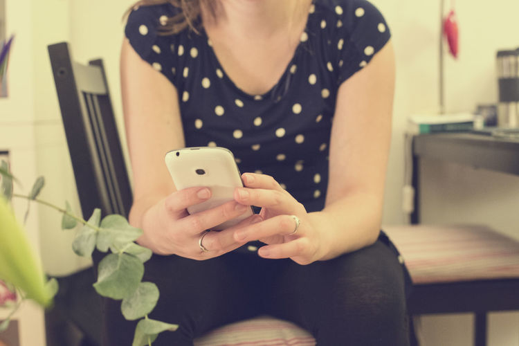 Young woman texting at home Chair Girl, Hand Holding, Home Indoors  Mid Section Part Of Person Phone Real People Room Student,bible,bus Texting WhatsApp Woman Young