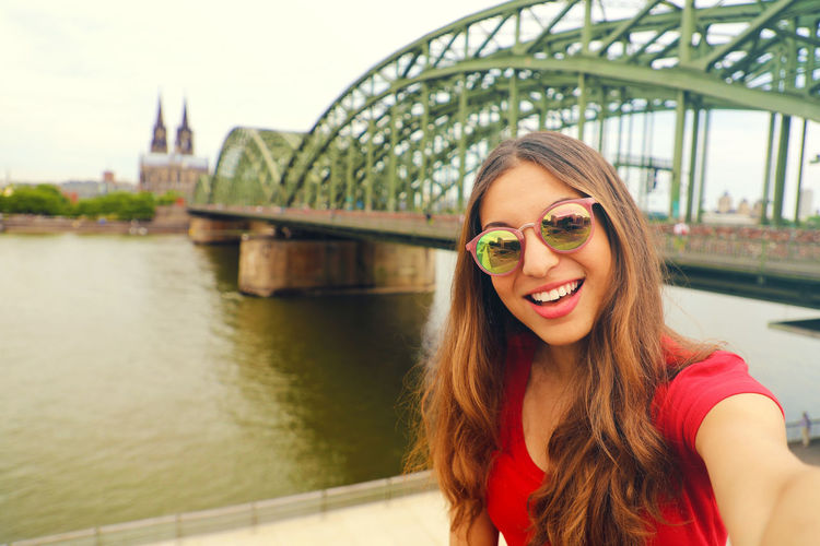 Selfie woman in Cologne Cologne Cologne , Köln,  Köln Architecture Beautiful Woman Bridge Bridge - Man Made Structure Built Structure City Fashion Hairstyle Happiness Leisure Activity Lifestyles Long Hair Looking At Camera One Person Outdoors Portrait Smiling Sunglasses Tourism Travel Destinations Young Adult Young Women