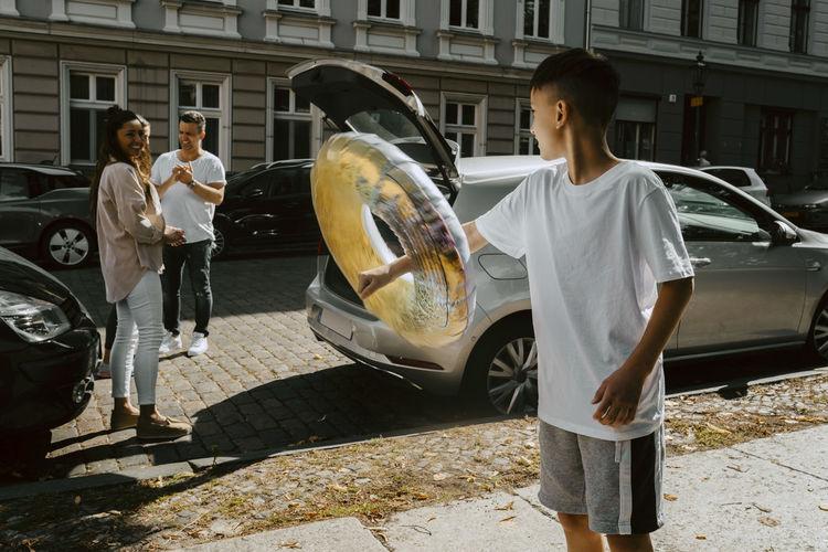 People standing by car on sidewalk in city