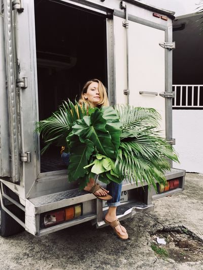 Attractive blond woman sits in the back of a delivery truck with a large bouquet of tropical plant leaves Beauty In Nature Beautiful Woman Attractive Beautiful Woman Plant Life Florist Monstera Deliciosa Tropical Plants Tropical One Person Real People Full Length Architecture Plant Casual Clothing Leisure Activity Nature Gardening Portrait Day Women Green Color Outdoors