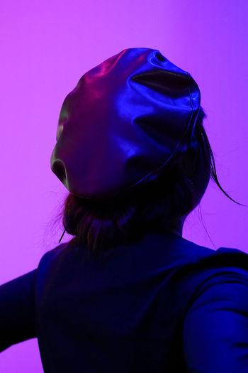 Close-up portrait of woman against blue background