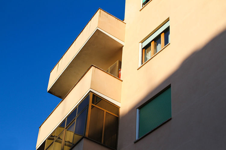 Urban construction in rome, residential building, painted yellow, blue sky.