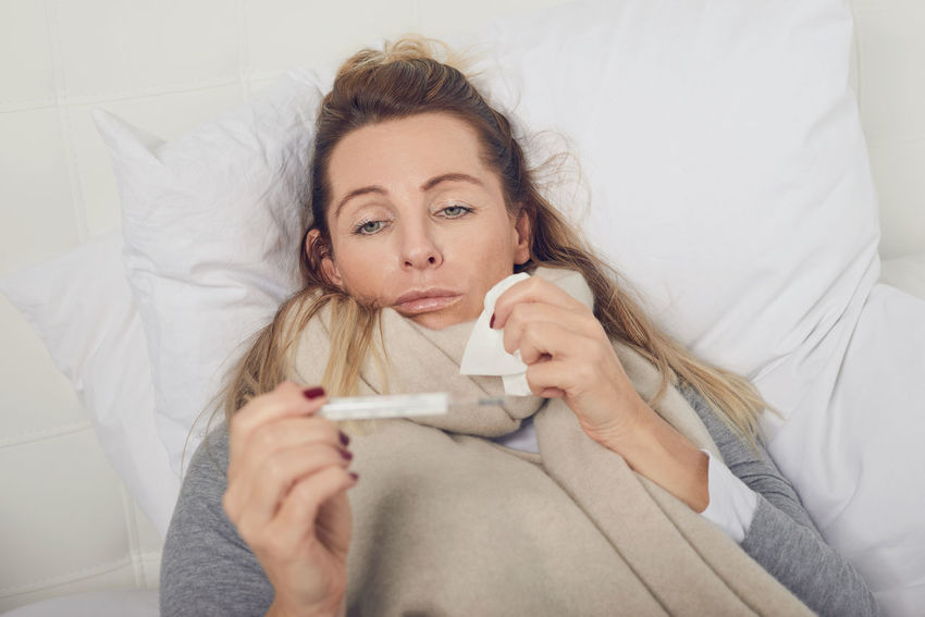Sick woman looking at a fever thermometer Bed FLU AND COLD SEASON Medicine Woman Cold Face Fever Flu Health Care Illness Portrait Sickness Thermometer