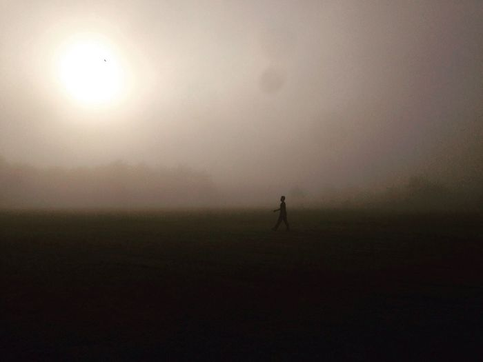 Silhouette of person on field against sky