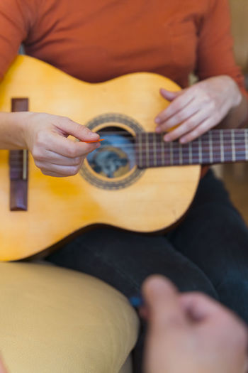 Midsection of woman playing guitar in home