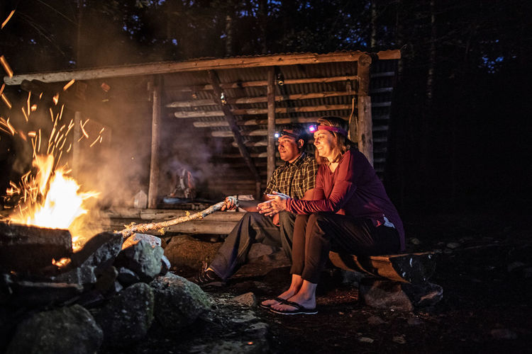 People sitting on wooden log at night