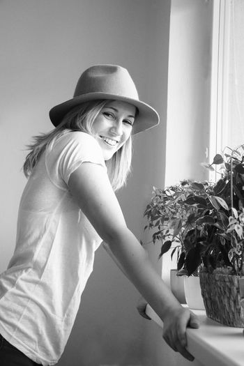 Portrait of smiling young woman wearing hat standing against wall