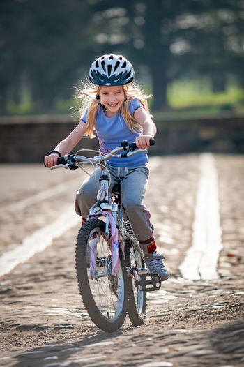 Cheerful girl riding bicycle on land